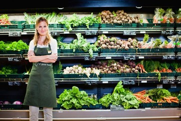 Grocer smiling in produce section